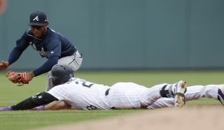 Colorado Rockies' Nolan Arenado, front, slides safely into second base with a double as Atlanta Braves second baseman Ozzie Albies turns to apply the tag in the first inning of a baseball game Thursday, Aug. 17, 2017, in Denver. (AP Photo/David Zalubowski)