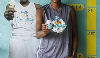 "WNBA player with the Atlanta Dream Angel McCoughtry stands next to a photo of herself inside her recently opened ice cream shop, ""McCoughtry's,"" located in metropolitan Atlanta. The two-time Olympic gold medalist is sitting out the 2017 WNBA season to recover physically from playing year-round in the U.S. and overseas for eight years. (AP Photo/Andy Buhler)"