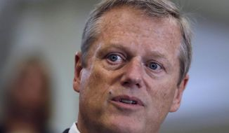 Republican Gov. Charlie Baker reads a portion of a proclamation, which he signed in response to the events at a white nationalist rally in Charlottesville last week, while joined by Democratic leaders at the Statehouse in Boston, Thursday, Aug. 17, 2017. Baker criticized comments made by President Donald Trump in the wake of the rally in which he appeared to equate the protesters, which included neo-Nazis, skinheads and Ku Klux Klan members, with counter-protesters. (AP Photo/Charles Krupa)