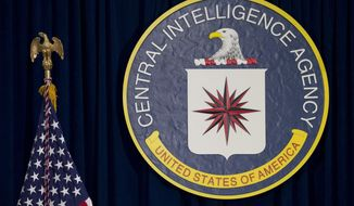 FILE - This April 13, 2016 file photo shows the seal of the Central Intelligence Agency at CIA headquarters in Langley, Va .A settlement was announced Thursday, Aug. 17, 2017, in a landmark lawsuit brought by the American Civil Liberties Union against two psychologists involved in designing the CIA's harsh interrogation program used in the war on terror. (AP Photo/Carolyn Kaster, File)