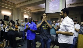 DeBraun Thomas, of Lexington, Ky., center, with the group Take Back Cheapside, reacts after the Lexington-Fayette Urban County Council unanimously voted to move two Confederate-era statues from downtown Lexington at the Lexington-Fayette Urban County Government Center in Lexington, Ky., Thursday, Aug. 17, 2017. Government leaders in Kentucky's second-largest city took a decisive stand Thursday night in favor of moving two Confederate statues from their prominent places outside a former courthouse being converted into a visitors center. (Alex Slitz/Lexington Herald-Leader via AP)