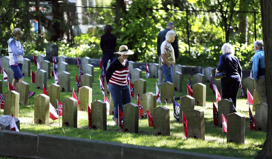 """FILE - in this May 29, 2017 file photo, attendees peruse the grave markers in the Confederate Rest section after Memorial Day ceremonies at Forest Hill Cemetery in Madison, Wis.  Mayor Paul Soglin says monuments to confederate soldiers are being removed from the cemetery in traditionally liberal Madison, Wisconsin, because the Civil War was """"a defense of the deplorable practice of slavery."""" Soglin made the announcement in a statement Thursday, Aug. 17.  (M.P. King/Wisconsin State Journal via AP)"""