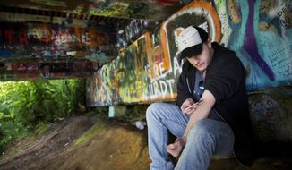 ADVANCE FOR USE MONDAY, AUG. 21, 2017 AND THEREAFTER-Forrest Wood, 24, injects heroin into this arm under a bridge along the Wishkah River at Kurt Cobain Memorial Park in Aberdeen, Wash., Tuesday, June 13, 2017. Wood grew up here, watching drugs take hold of his relatives, and he swore to himself that he would get out of this place, maybe spend his days in the woods as a park ranger. But he started taking opioid painkillers as a teenager, and before he knew it he was shooting heroin, a familiar first chapter in the story of American addiction. (AP Photo/David Goldman)