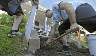 ADVANCED FOR RELEASE SATURDAY, AUGUST 19, 2017 Habitat for Humanity volunteers, Bryan Hilliard, 33, of Kittanning right and Drew Simmers, 28, also of Kittanning work at clearing a landing for porch steps at 249 Main Street in Parnasses section of New Kensington, Pa., Wednesday Aug. 2, 2017. (Louis B. Ruediger/Pittsburgh Tribune-Review via AP)