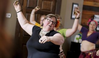 Ann Peterson, 60, of Altoona, leads part of an American style tribal belly dance on Wednesday, Aug. 9, 2017 during a Lasa Anahata Tribal class at Dragonfly Dance and Wellness in Eau Claire, Wis. (Marisa Wojcik/The Eau Claire Leader-Telegram via AP)
