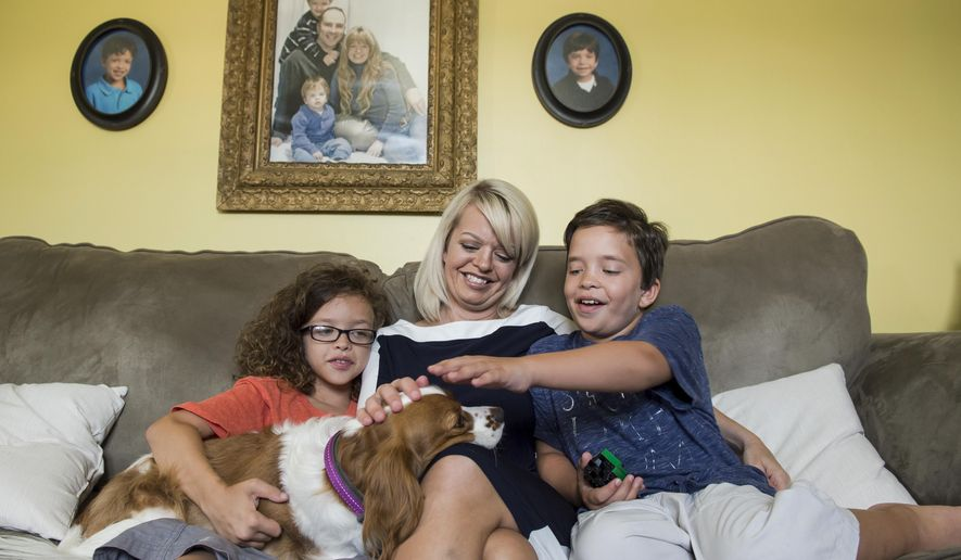 ADVANCE FOR SATURDAY AUG. 19 AND THEREAFTER -  In a July 21, 2017 photo, Anna Corbin sits between her two sons, Jackson, left, and Henry, as they play with their dog, Eloise, inside their Hanover, Pa., home. Henry, 9, and Jackson, 11, both have Noonan syndrome, a genetic disorder that affects various systems of the body.  (Dan Rainville/The Evening Sun via AP)