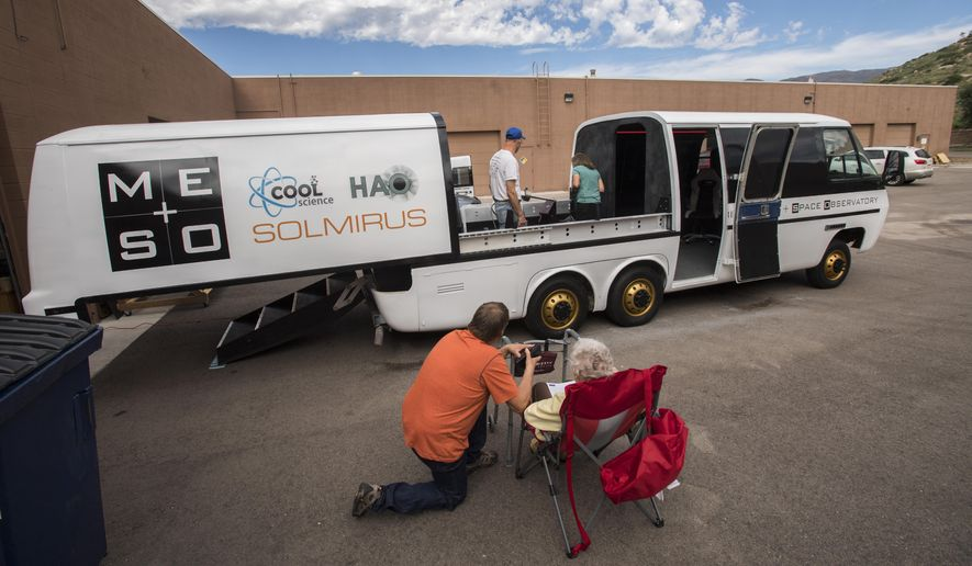 ADVANCE FOR WEEKEND EDITIONS, AUG. 19-20 - In this Tuesday, Aug. 15, 2017 photo Agnes Busch, 90, the former owner of the 1976 GMC recreational vehicle that was converted into the Mobile Earth & Space Observatory, watches as people tour the mobile observatory outside the MESO office in Colorado Springs, Colo. A team from the Pikes Peak Observatory that will drive it to Nebraska to participate in the Citizen CATE project that will document the solar eclipse on Monday. (Christian Murdock/The Gazette via AP)