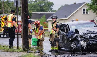 Emergency personnel work at the scene of a fatal accident near the intersection of Broadway Avenue and Huizenga Street in Norton Shores, Mich. on Thursday, Aug. 17, 2017. The crash occurred shortly after a police officer was ordered to stop pursuing a stolen vehicle suspected to be involved in a shoplifting complain at a Meijer store. The suspect driver and a passenger in the other vehicle were taken to the hospital, Gale said. The other driver died at the scene. (Kaytie Boomer/Muskegon Chronicle via AP)