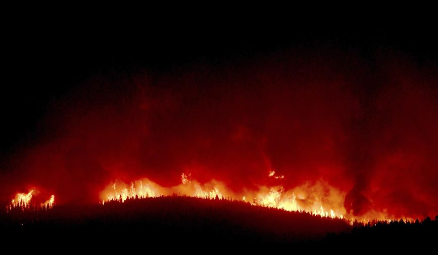 A wall of flames hundreds of feet high burn on a ridge above Rowan Road south of Lolo, Montana, early Thursday, Aug. 17, 2017. About 400 homes south and west of Lolo were evacuated because of the proximity of the Lolo Peak fire. (Kurt Wilson /The Missoulian via AP)