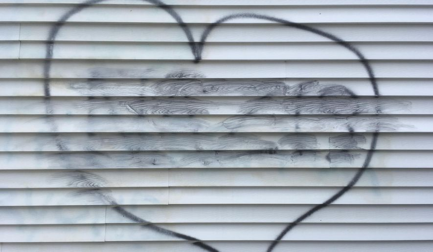 """The word """"NAZIS"""", smudged from a cleaning attempt, appears in the center of a heart symbol on the wall of a building, which houses the New Hampshire Republican Party, in Concord, N.H., Thursday Aug. 17, 2017. A party advisor is blaming """"malcontents"""" for the vandalism. (AP Photo/Mike Casey)"""