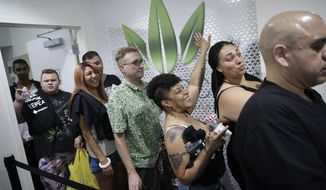 FILE- In this July 1, 2017 file photo, people wait in line at the Essence cannabis dispensary in Las Vegas. A judge cleared the way Thursday, July 17, for Nevada to allow more businesses to move marijuana from growers to stores in an effort to keep up with overwhelming demand since recreational pot sales began last month. (AP Photo/John Locher, File)