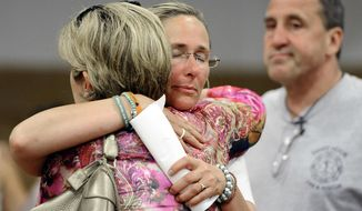 FILE - In this July 11, 2013 file photo, Scarlett Lewis, center, mother of Sandy Hook Elementary School shooting victim Jesse Lewis, hugs Lynn McDonnell, left, mother of victim Grace McDonnell, as Neil Heslin, right, father of Jesse Lewis watches after a public forum in Newtown, Conn. Lawyers for Lewis, Heslin and Leonard Pozner, father of Noah Pozner who also was killed in the school shooting, filed motions Tuesday, Aug. 15, 2017, in Danbury Superior Court seeking to see evidence that two teachers fatally shot in the massacre had access to keys that could have been used to lock their classroom doors. (AP Photo/Jessica Hill)