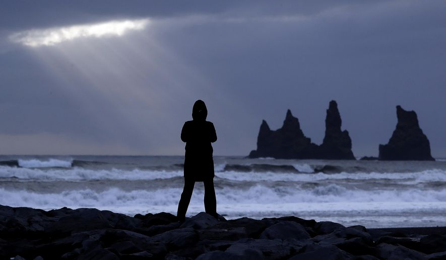In this Oct. 28, 2016, file photo, a woman stands on the black beach in Vik, Iceland, near the Volcano Katla. The AP reported that stories claiming the Icelandic government will pay immigrants $5,000 a month to marry Icelandic women are hoaxes. (AP Photo/Frank Augstein, File)