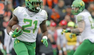 FILE - In this Nov. 26, 2016, file photo, Oregon running back Royce Freeman (21) carries during the first half of an NCAA college football game against Oregon State in Corvallis, Ore. After the trials of last season, Freeman appears to have emerged with two things: a college degree and a bright outlook. (AP Photo/Timothy J. Gonzalez, File)