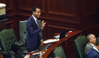 "In this May, 31, 2017 file photo, Rep. Christian Mitchell, D-Chicago, speaks on the House floor at the Capitol in Springfield, Ill. A political cartoon circulated by a conservative Illinois think tank with ties to Republican Gov. Bruce Rauner has triggered accusations of racism and insensitivity. The rendering depicted a black school child from Chicago begging for money from a cigar-smoking white man in a suit. ""There is a way to make a policy point that's legitimate, but not in a way that caricatures African Americans and provokes a dark history,"" said Mitchell.(Rich Saal/The State Journal-Register via AP)"