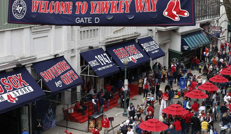FILE - In this April 4, 2014 file photo, fans enjoy pre-game festivities along Yawkey Way outside Fenway Park in Boston. Boston Red Sox principal owner John Henry says he wants to take steps to rename all of Yawkey Way, a street that has been an enduring reminder of the franchise's complicated racial past. (AP Photo/Michael Dwyer, File)