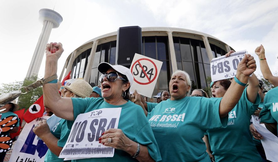 FILE - In this June 26, 2017, file photo, Lydia Balderas, left, and Merced Leyua, right, join others as they protest against a new sanctuary cities bill outside the federal courthouse in San Antonio. Even as a new Texas law targeting so-called sanctuary cities remains in legal limbo, police chiefs and sheriffs are making changes to comply, rewriting training manuals and withdrawing policies that prevented officers from asking people whether they're in the United States illegally. The law, known as Senate Bill 4, goes into effect Sept. 1 unless a federal judge in San Antonio blocks it. (AP Photo/Eric Gay, File)