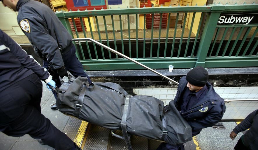FILE - In this Jan. 22, 2013 file photo, a police officer and medical examiner personnel carry a body out of the Times Square subway station in New York after witnesses told police that the man who died jumped into the path of an oncoming train. It's a largely overlooked but gory reality of the New York City subway system: When someone kills themselves by jumping in front of a train, police need to find a place to put the mutilated body until a medical examiner truck arrives. Sometimes, transit workers say, that place is their break room or bathrooms, and some say they have been traumatized by unexpectedly coming upon a stowed body.(AP Photo/Seth Wenig, FIle)