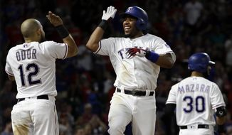 Texas Rangers' Rougned Odor (12) and Elvis Andrus, center, celebrate a solo home run by Andrus as Nomar Mazara (30) walks to the plate during the fifth inning of a baseball game against the Detroit Tigers on Wednesday, Aug. 16, 2017, in Arlington, Texas. (AP Photo/Tony Gutierrez)