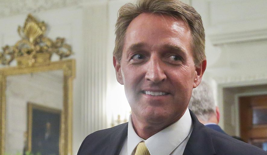 In this photo taken July 19, 2017, Sen. Jeff Flake, R-Ariz. walks to his seat as he attends a luncheon with other GOP Senators and President Donald Trump at the White House in Washington.  Bombarded by the sharpest attacks yet from fellow Republicans, President Donald Trump on Thursday, Aug. 17, 2017, dug into his defense of racist groups by attacking members of own party and renouncing the rising movement to pull down monuments to Confederate icons. (AP Photo/Pablo Martinez Monsivais)