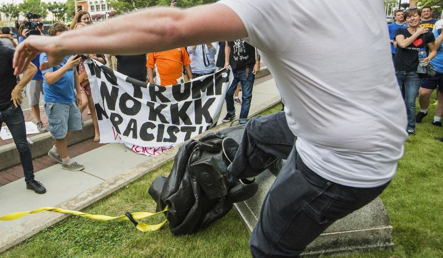 FILE - In this Aug. 14, 2017 file photo, a protester kicks the toppled statue of a Confederate soldier after it was pulled down in Durham, N.C.  Bombarded by the sharpest attacks yet from fellow Republicans, President Donald Trump on Thursday, Aug. 17, 2017, dug into his defense of racist groups by attacking members of own party and renouncing the rising movement to pull down monuments to Confederate icons.  (Casey Toth/The Herald-Sun via AP, File)/The Herald-Sun via AP)
