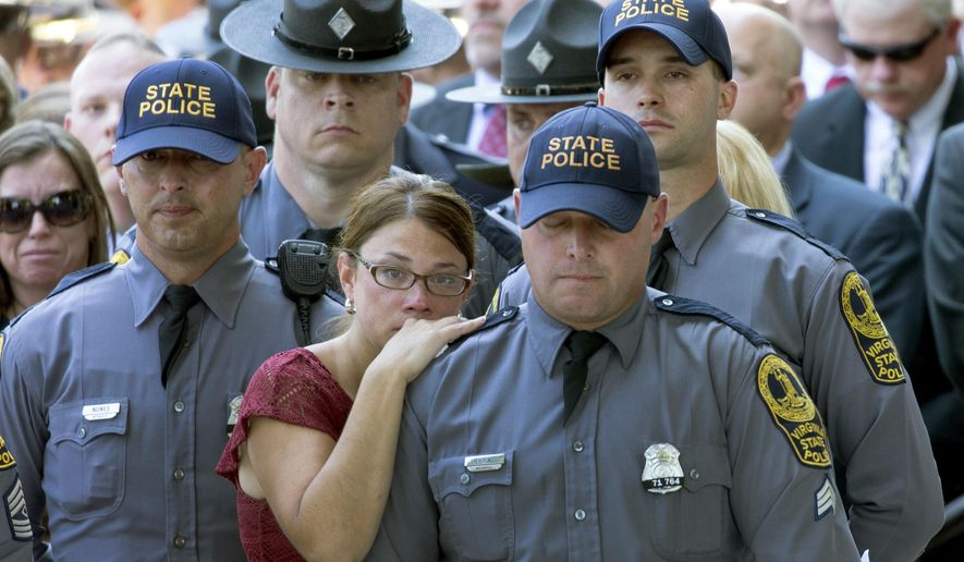 Susanne Kain, center left, comforts her husband, Virginia State Police Sgt. CM Kain, center right, during the funeral of Virginia State Trooper-Pilot Berke Bates at St. Paul's Baptist Church in Richmond, Va., on Friday, Aug. 18, 2017. Bates died in a fatal crash of a helicopter that had been monitoring a violent white-nationalist protest in Charlottesville, Va. (Daniel Sangjib Min/Richmond Times-Dispatch via AP)