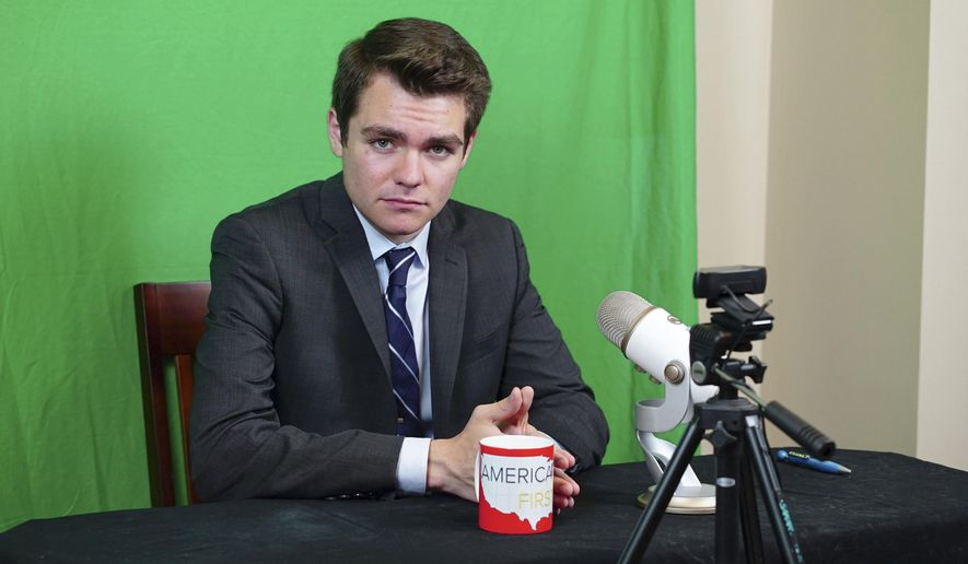 """Nicholas Fuentes, poses for a photo in his basement studio in LaGrange Park, Ill., Wednesday, Aug. 16, 2017. The 18-year-old student who attended the white nationalist rally in Virginia last weekend says he has withdrawn from college in Boston in part because of death threats. The studio is where Fuentes records his YouTube show """"America First."""" (AP Photo/Teresa Crawford)"""