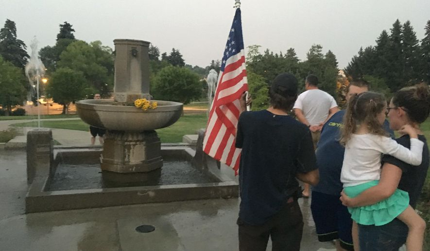 Andrew Perl holds an American flag in front of a Confederate memorial on Thursday, Aug. 17, 2017, in Helena, Mont., as Marlee Hanson looks on while holding her daughter. About two dozen people gathered to protest after city workers made initial preparations to dismantle the granite fountain commissioned by the Daughters of the Confederacy more than a century ago (AP Photo/Matt Volz)
