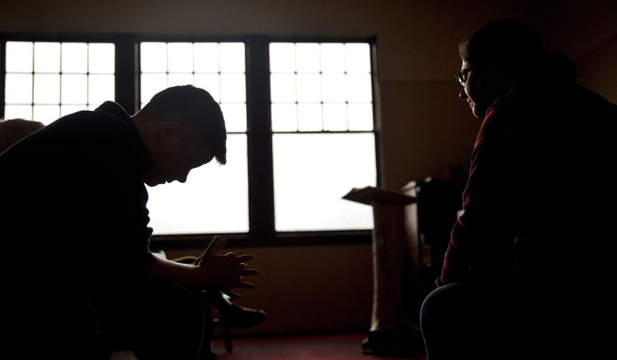 "Aaron Scott, left, prays during a service conducted by Rev. Sarah Monroe, right, at Chaplains on the Harbor church in Westport, Wash., Thursday, June 15, 2017. ""I don't think our politicians know how high the stakes are here, and after so many years have gone by with our situation still as devastated as it is, I don't know if they care,"" Monroe says. ""I'm not sure how much worse it can get, and at the same time I'm afraid to see how much worse it can get."" (AP Photo/David Goldman)"