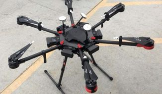 This undated photo provided by the U.S. Border Patrol shows a 2-foot-high drone that a border patrol agent spotted swooping over the border fence on Tuesday, Aug. 8, 2017, near a San Diego border crossing. Authorities have arrested a man they say used the drone to fly drugs across the Mexican border into California. (U.S. Border Patrol via AP)