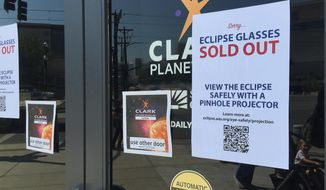 An eclipse glasses sold out sign is posted outside the Clark Planetarium main doors advising people to safely view the eclipse with a pinhole projector after the planetarium ran out of glasses Thursday, Aug. 17, 2017, in Salt Lake City. (AP Photo/Brady McCombs)