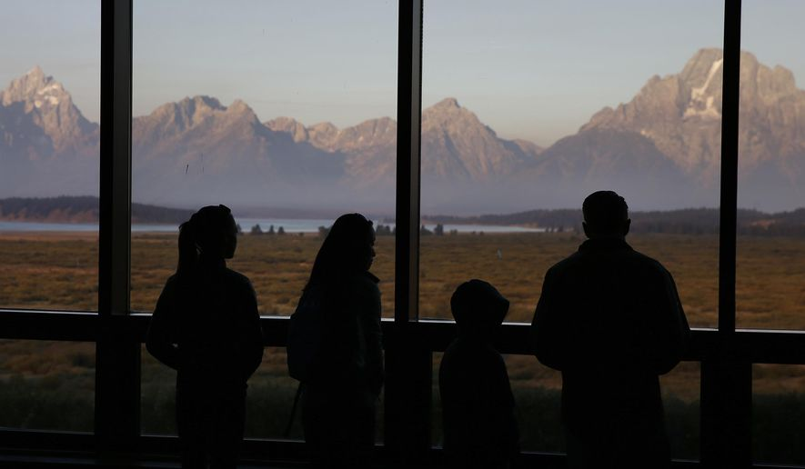 FILE- In this Aug. 28, 2016 file photo, visitors watch the morning sun illuminate the Grand Tetons, partially-obscured by smoke from nearby wildfires, as seen from within the Great Room at the Jackson Lake Lodge, in Grand Teton National Park, north of Jackson Hole, Wyo. Grand Teton National Park, normally in the shadow of the neighboring and world-renowned Yellowstone National Park in northwest Wyoming, is set to get its day in the sun with next week's total solar eclipse passing directly over the park. (AP Photo/Brennan Linsley, File)