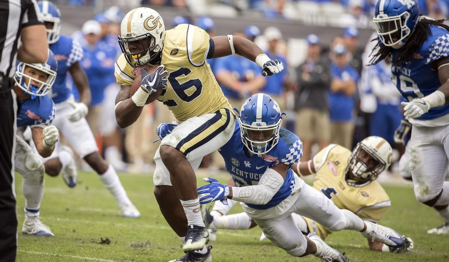FILE - In this Dec. 31, 2016 file photo, Georgia Tech running back Dedrick Mills (26) is tackled by Kentucky safety Mike Edwards (27) during the second half of the TaxSlayer Bowl NCAA college football game in Jacksonville, Fla. Mills has been kicked off the team for a violation of athletic department rules, the school announced Friday, Aug. 18, 2017.(AP Photo/Stephen B. Morton, File)