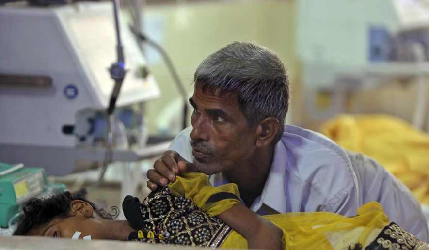 In this Aug. 13, 2017 file photo, a relative attends to a child receiving treatment at the state-run Baba Raghav Das Medical College Hospital in Gorakhpur, Uttar Pradesh, India. Acute encephalitis syndrome is a catch-all term to describe patients suffering fever, vomiting, headaches and brain function issues such as confusion, trouble speaking and coma along with seizures. (AP Photo/Rajesh Kumar Singh, File)