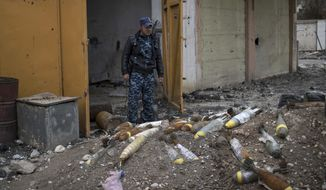 FILE- In this March 22, 2017, file photo, a Federal Police stands next to unexploded bombs left by Islamic State group militants on the western side of Mosul, Iraq. On Thursday, Aug. 17, the top U.S. commander in Iraq said for the first time that the American military will help contractors and other officials locate unexploded bombs dropped by the coalition. U.S. Embassy officials have asked the coalition to declassify grid coordinates for bombs dropped in Iraq to help clear the explosives. The coalition's unexploded bombs are only a small part of Mosul's problems. The bulk of the explosives have been hidden by IS fighters to be triggered by the slightest movement, even picking up a seemingly innocent children's toy, lifting a vacuum cleaner, or opening an oven door. (AP Photo/Felipe Dana, File)