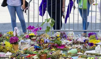 People visit a memorial at the site in Charlottesville, Va., on Friday, Aug. 18, 2017, where Heather Heyer was killed. Heyer was struck by a car while protesting a white nationalist rally on Saturday Aug. 12. (AP Photo/Cliff Owen)