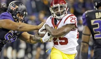 FILE - In this Nov. 12, 2016 file photo, Washington defensive lineman Vita Vea, left, pushes Southern California running back Ronald Jones II on a carry by Jones in the first half of an NCAA college football game in Seattle. Ronald Jones II is one in a group of Heisman longshots who could end up contending for the award, which will be announced on Dec. 9 in New York.(AP Photo/Elaine Thompson, File)
