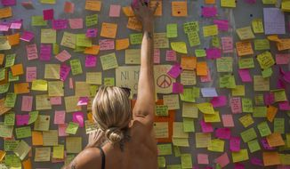 A woman leaves a message as a memorial tribute to the victims on Barcelona's historic Las Ramblas promenade Friday Aug. 18, 2017. Police on Friday shot and killed five people carrying bomb belts who were connected to the Barcelona van attack, as the manhunt intensified for the perpetrators of Europe's latest rampage claimed by the Islamic State group. (AP Photo/Santi Palacios)