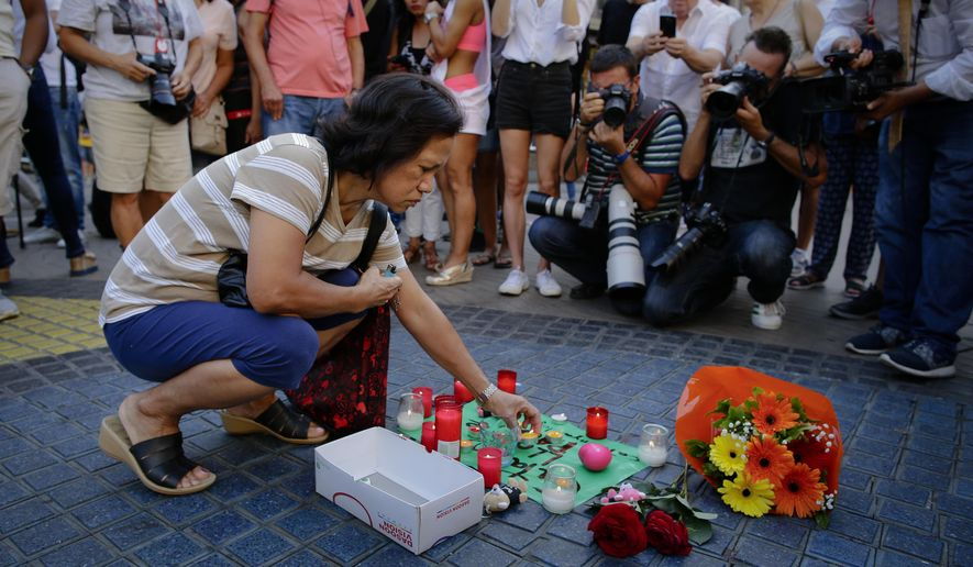 """A woman places a candle on a paper that reads """"Catalunya - place of peace"""" in Las Ramblas, Barcelona, Spain, Friday, Aug. 18, 2017. Spanish police on Friday shot and killed five people carrying bomb belts who were connected to the Barcelona van attack that killed at least 13, as the manhunt intensified for the perpetrators of Europe's latest rampage claimed by the Islamic State group. (AP Photo/Manu Fernandez)"""
