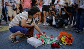 "A woman places a candle on a paper that reads ""Catalunya - place of peace"" in Las Ramblas, Barcelona, Spain, Friday, Aug. 18, 2017. Spanish police on Friday shot and killed five people carrying bomb belts who were connected to the Barcelona van attack that killed at least 13, as the manhunt intensified for the perpetrators of Europe's latest rampage claimed by the Islamic State group. (AP Photo/Manu Fernandez)"