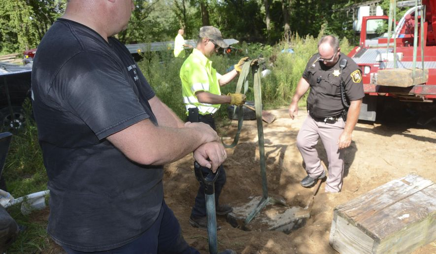 Authorities work with Bud's Towing on Thursday, Aug. 17, 2017, to recover a child's gravestone that was reported stolen in June and found buried in the backyard of a home in Emmett Township, Mich.  The gravestone was for a 2-year-old boy who died in 1988 and was reported stolen in June from Banfield Cemetery in Barry County, Mich., authorities said.  (Trace Christenson/Battle Creek Enquirer via AP)