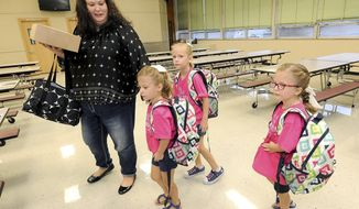 From left,  Jayme Harper leads her triplets, Lauren, Regan and Addison into the cafeteria on their first day of school on Thursday, Aug. 17, 2017 at Jefferson Elementary in Joplin, Mo. The Triplets born just five days before a deadly tornado slammed Joplin in 2011 have started school.   (Laurie Sisk/The Joplin Globe via AP)