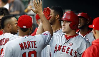 Los Angeles Angels' Mike Trout, right, high-fives teammate Jefry Marte after hitting a solo home run in the first inning of a baseball game against the Baltimore Orioles in Baltimore, Saturday, Aug. 19, 2017. (AP Photo/Patrick Semansky)