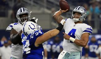 Dallas Cowboys guard Jonathan Cooper, left, helps against a rush from Indianapolis Colts defensive tackle David Parry (54) as quarterback Dak Prescott (4) throws a pass in the first half of a preseason NFL football game, Saturday, Aug. 19, 2017, in Arlington, Texas. (AP Photo/Ron Jenkins)