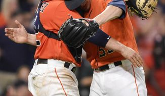 Houston Astros relief pitcher Ken Giles, right, hugs catcher Max Stassi after their win over the Oakland Athletics in a baseball game, Friday, Aug. 18, 2017, in Houston. (AP Photo/Eric Christian Smith)