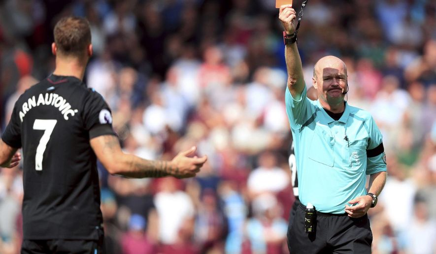 Referee Lee Mason, right, shows a red card to West Ham United's Marko Arnautovic during the English Premier League soccer match between Southampton and West Ham,  at St Mary's, in Southampton, England, Saturday, Aug. 19, 2017. (Adam Davy/ PA via AP)