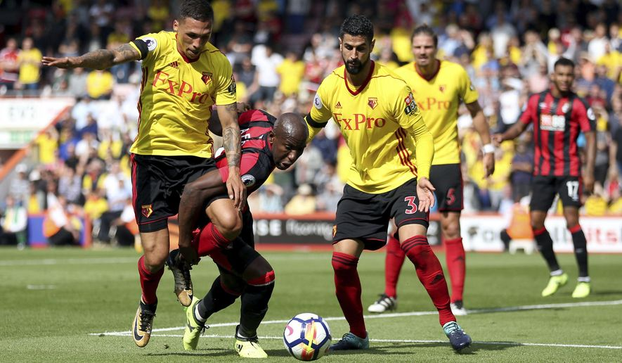 AFC Bournemouth's Benik Afobe, second left, goes down in the area under the challenge from Watford's Jose Holebas during their English Premier League soccer match at the Vitality Stadium, Bournemouth, England, Saturday, Aug. 19, 2017. (Steven Paston/PA via AP)