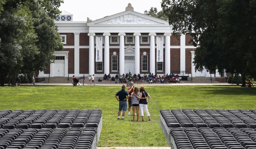 A family takes photographs during first year move-in day while on the Lawn of the University of Virginia, Friday, Aug. 18, 2017, in Charlottesville, Va., a week after a white nationalist rally took place on there. (AP Photo/Jacquelyn Martin)