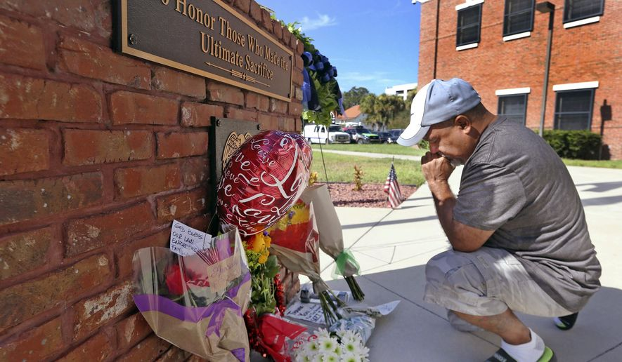 CORRECTS STATUS OF SECOND POLICE OFFICER - After placing flowers at a makeshift memorial, Miguel Velez, say's a prayer for the officer that was killed on Saturday, Aug. 19, 2017 in Kissimmee, Fla.   The Kissimmee Police Department says Sgt. Sam Howard died Saturday from his injuries. His colleague, Officer Matthew Baxter, died Friday night after the attack in a neighborhood of Kissimmee, located south of the theme park hub of Orlando.   (Red Huber/Orlando Sentinel via AP)