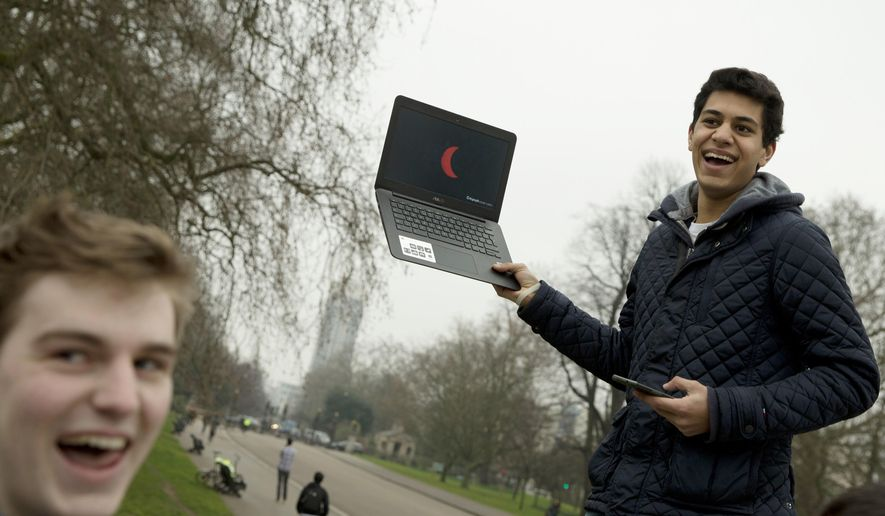 FILE - In this Friday, March, 20, 2015 file photo, a student holds up a laptop computer with a live television feed showing the progress of total solar eclipse to a group of his friends, near the Albert Memorial in London. For the 2017 eclipse in the United States, NASA and other news and television outlets will offer live coverage of the celestial event. (AP Photo/Alastair Grant)